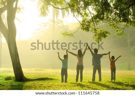 an asian family jumping in joy in the park during a beautiful sunrise, backlight - stock photo