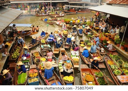 BANGKOK –  APRIL 13: Wooden boats busy ferrying people at Amphawa floating market on April 13, 2011 in Bangkok. A traditional popular method of buying and selling still practiced in Amphawa canals of Thailand. - stock photo