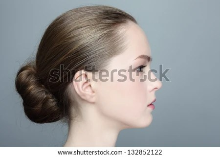 Profile Portrait Of Young Beautiful Girl With Hair Bun