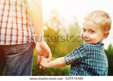 Father and son holding hand in hand - stock photo