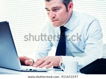 Insurance investigator on his laptop, following a lead on a fraudulent claim. Business, insurance, corporate and career concept