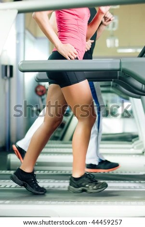 stock photo : Woman and man in gym - only legs to be seen - exercising running on the treadmill to gain more fitness; motion blur in limbs for dynamic