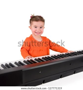 One small little girl learning to play piano. Isolated objects. - stock photo