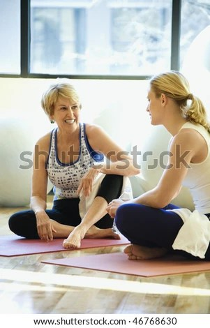 stock photo : Women sitting on exercise mats and enjoying a conversation at the gym. There are exercise balls behind them. Vertical shot.