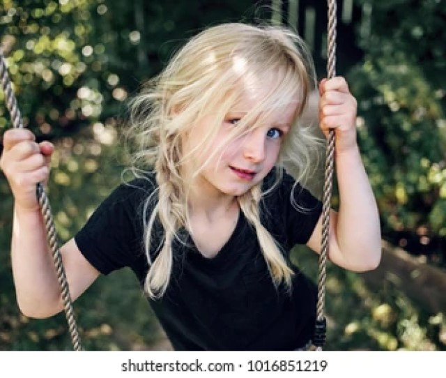 Adorable Little Blonde Girl Playing By Herself On A Tree Swing In Her Backyard On A