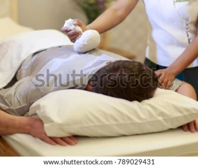 Asian Man Getting Thai Herbal Hot Compress Massage In Spa