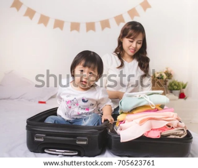 Asian Mom And Baby Girl With Suitcase Baggage And Clothes Ready For Traveling On Vacation