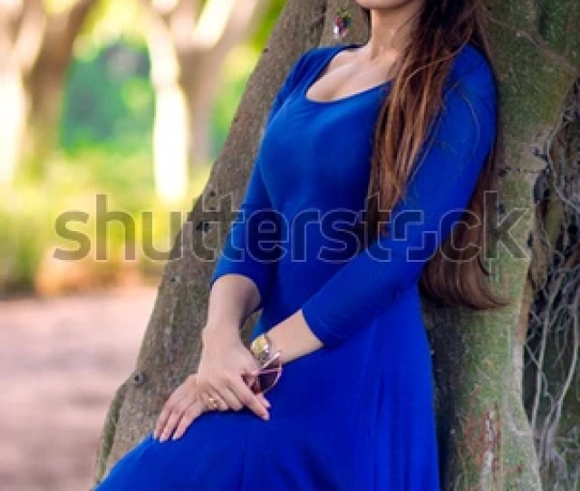 Beautiful Indian Girl In A Blue Dress Leaning Against An Old Tree In An Outdoor Park