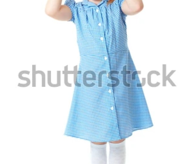 Blonde Schoolgirl In Blue Dress And Pigtails Makes Some Funny Faces Shoot Over White Background