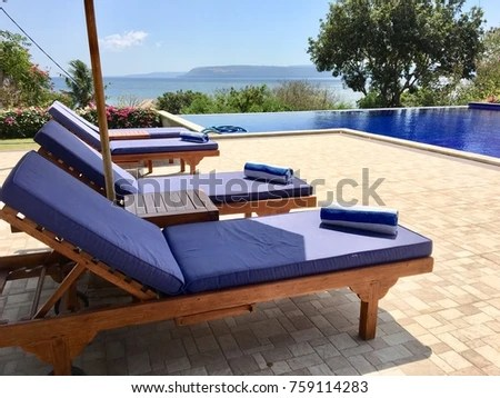 poolside lounge chairs white chair and a half with ottoman blue pool umbrella on stock photo edit now 759114283