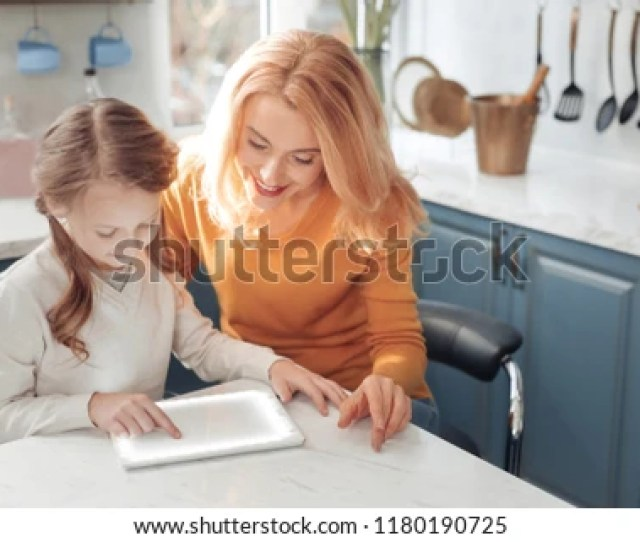 Kind Girl Bowing Head While Playing With Her Gadget