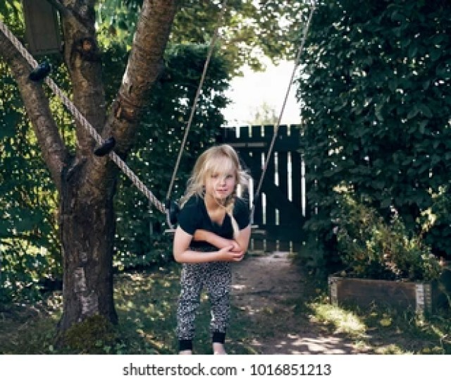 Cute Little Blonde Girl Playing By Herself On A Tree Swing In Her Backyard On A