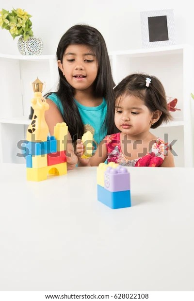 Cute little Indian/asian girls enjoying while playing with toys or blocks, sitting at table