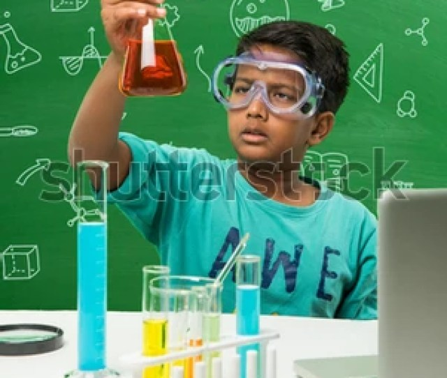 Cute Little Indian Asian School Boy Student Experimenting Or Studying Science In Laboratory Over