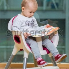 Toddler Reading Chair Office Gym Ball Little Baby Girl Book Stock Photo Edit Now On Knees In A High At Home By The