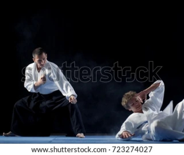 Martial Arts Aikido Master Wearing Hakamas Teaches His Young Student How To Defend Himself Against An
