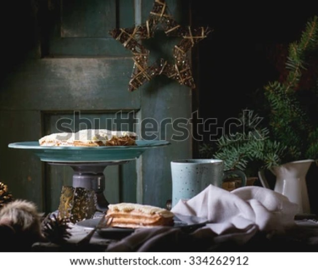 Old Wooden Christmas Table With Butter Cream Eclairs And Mug Of Hot Tea Decorating By
