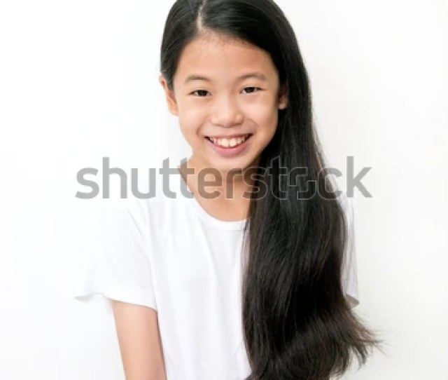 Portrait Of Beautiful Young Asian Teenage Girl With Long Wavy Black Hair On White Background