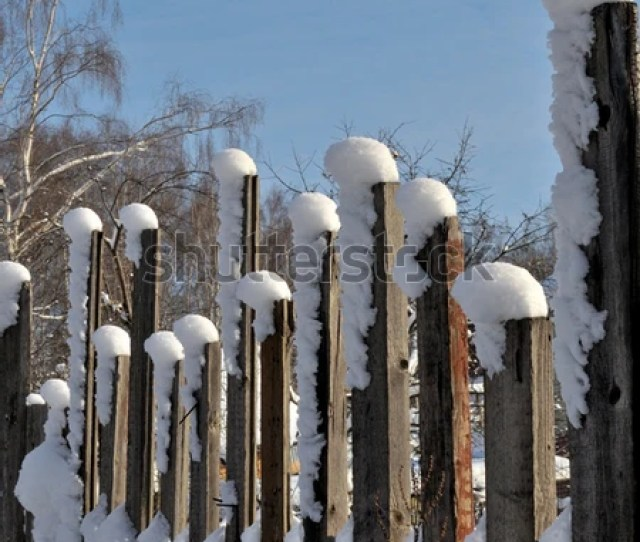Rough Homemade Fence Of Rough Boards After A Snowfall Covered With Snow Against The Blue Sky