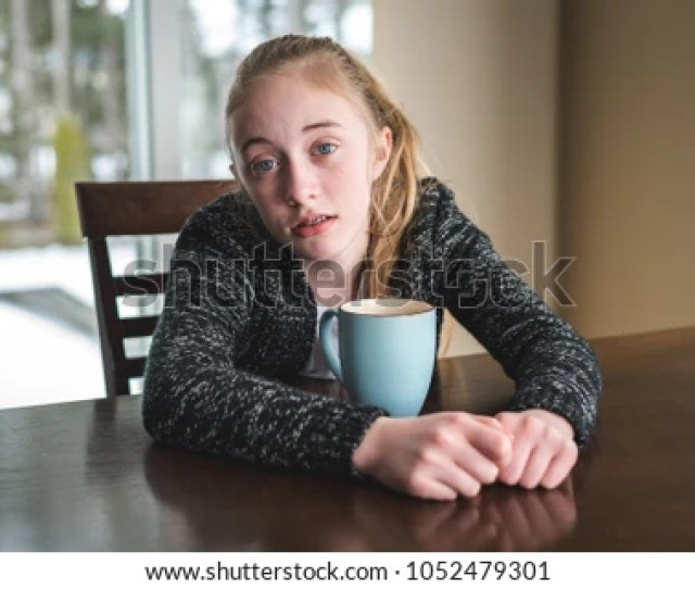 Sad Teen Girl Drinking Hot Chocolate Coffee Or Tea At A Table