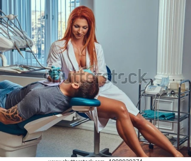 A Sexy Hot Redhead Dentist Woman Taking Care Of Her Patient