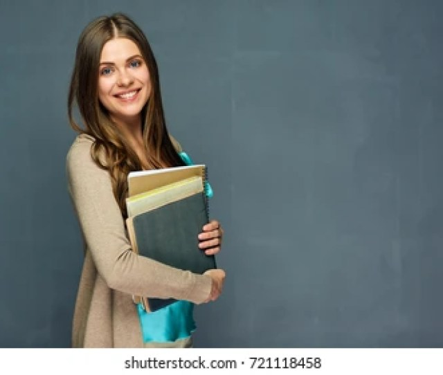 Smiling Girl Student Or Woman Teacher Portrait On Gray Wall