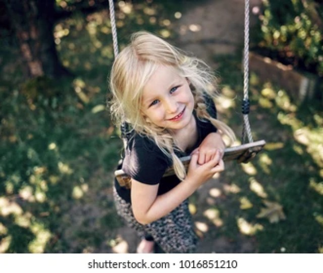 Smiling Little Blonde Girl Playing By Herself On A Tree Swing In Her Backyard On A