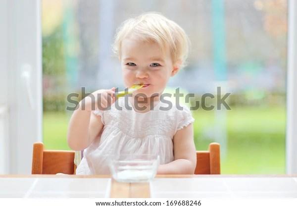 Smiling Little Blonde Toddler Girl Eating Stock Photo (Edit Now) 169688246