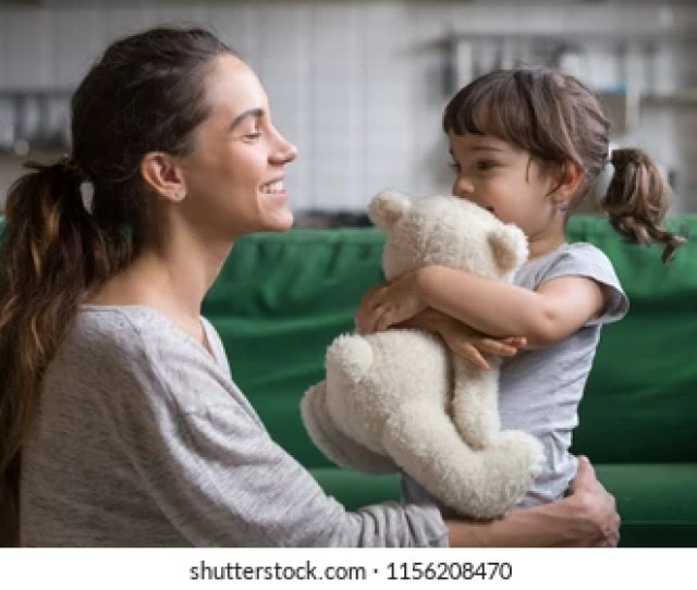 Smiling Mother Hugging Cute Little Girl Holding Teddy Bear Toy Showing Love And Care In Family
