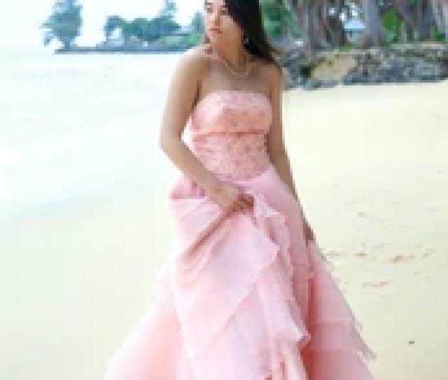Teen Girl Or Young Biracial Woman On Hawaiian Beach Wearing Long Flowing Pink Dress Or Gown