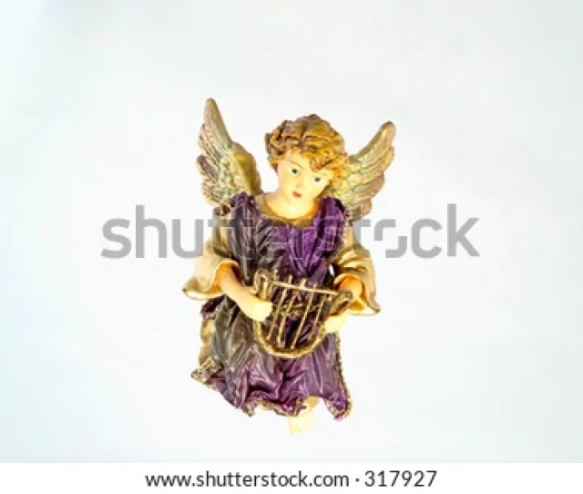 This Is A Christmas Ornament Of A Ceramic Angel Holding A Harp Against A Light Blue