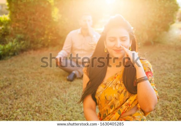 Two Indian people doing pranayama breathing techniques in the park outside