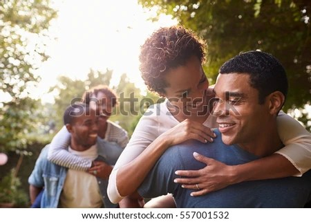 Two Young Adult Black Couples Having Fun Piggybacking