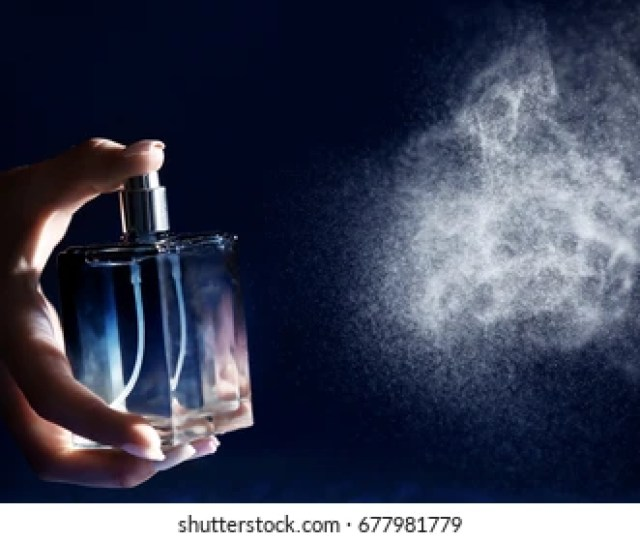 Woman Spraying Perfume On Dark Background Closeup