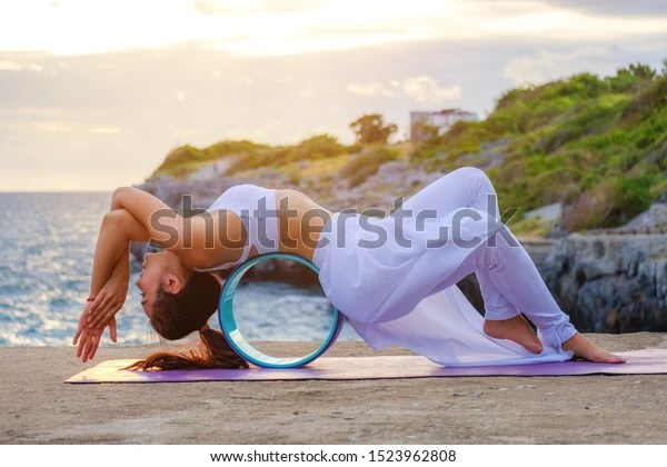 Yoga with wheel. Woman Yoga. Woman practice meditation at the coast. Relex in nature.