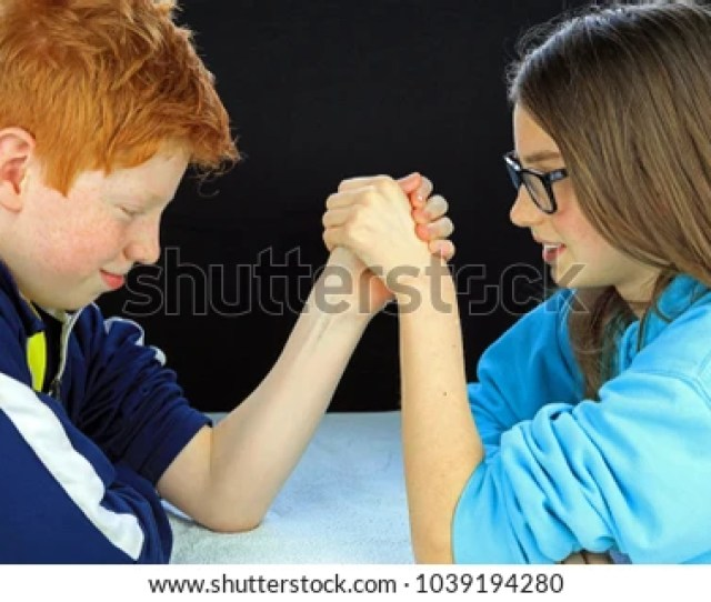 Young Boy And Girl Having An Arm Wrestle Brother And Sister In A Rival Battle