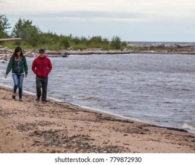 A Young Couple Hikes Along The Shores Of Great Slave Lake In Hay River Northwest