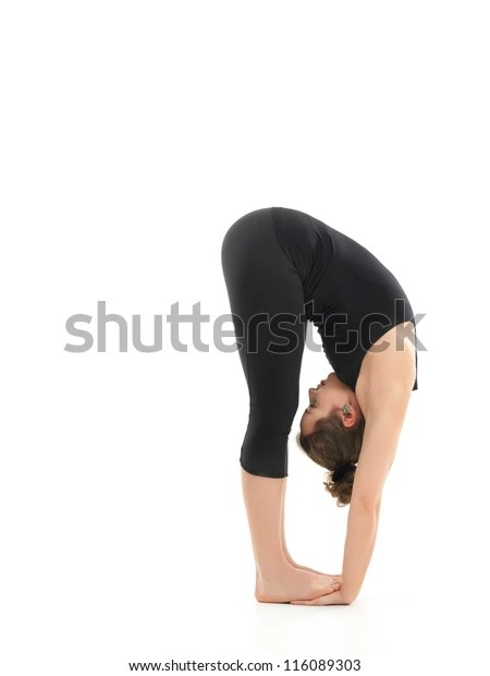 young girl in difficult forward bending yoga posture, dressed in black, on white background
