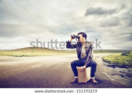 young man looks with binoculars sitting on a suitcase in the middle of a deserted road