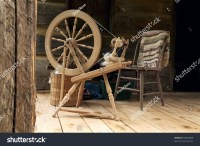 A Spinning Wheel With Yarn Baskets And Old Chair On A Log ...