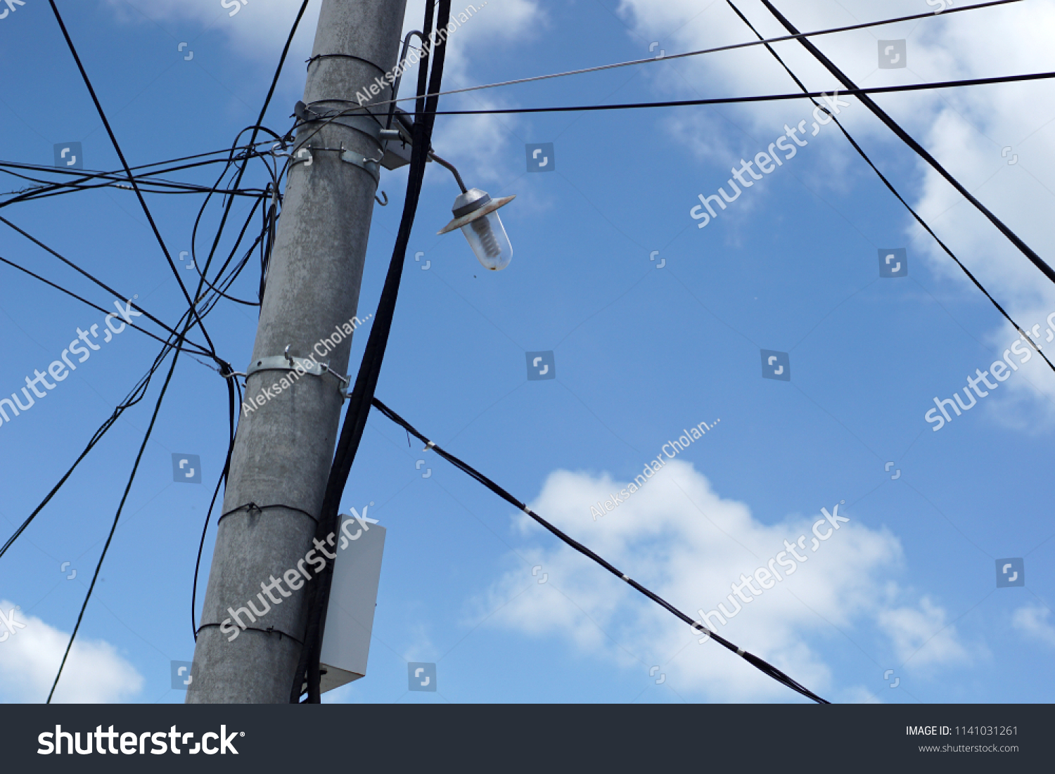 hight resolution of a telephone cable messy net against a blue sky