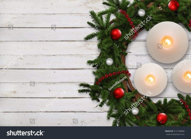 Advent wreath with christmas tree sprigs and candles on wooden planks.