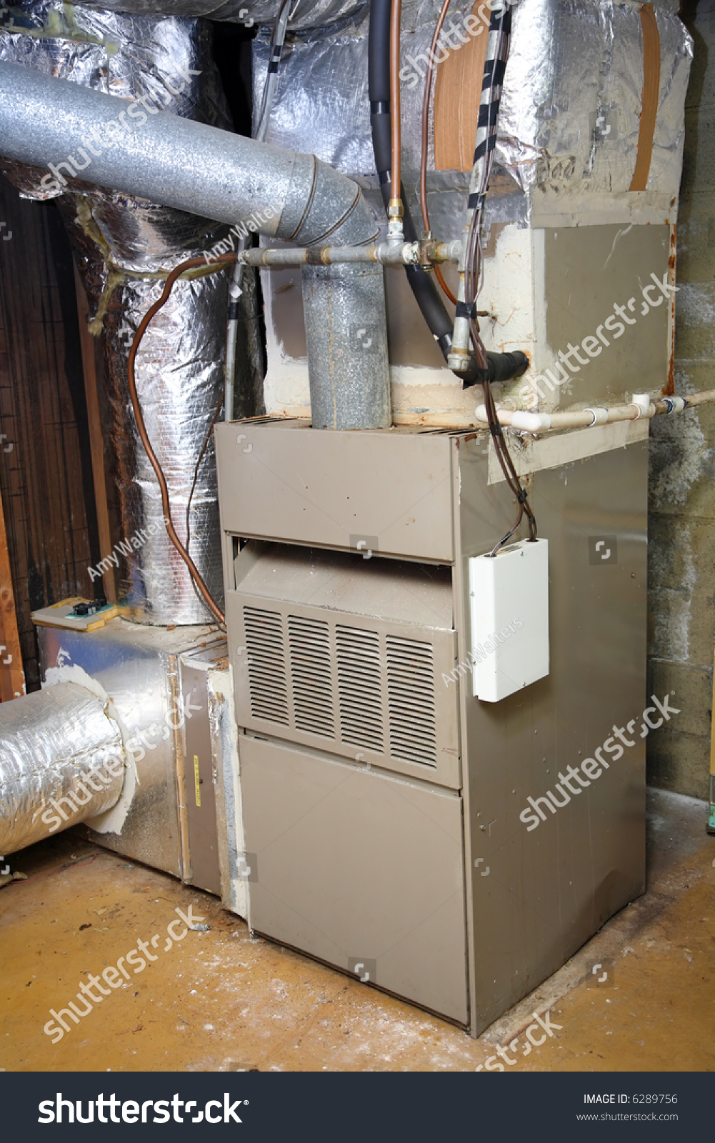An Old Gas Furnace In A Dirty Basement Stock Photo