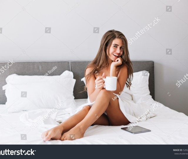 Attractive Girl With Naughty Shoulders And Legs Drinking Coffee On Bed In The Morning In Modern