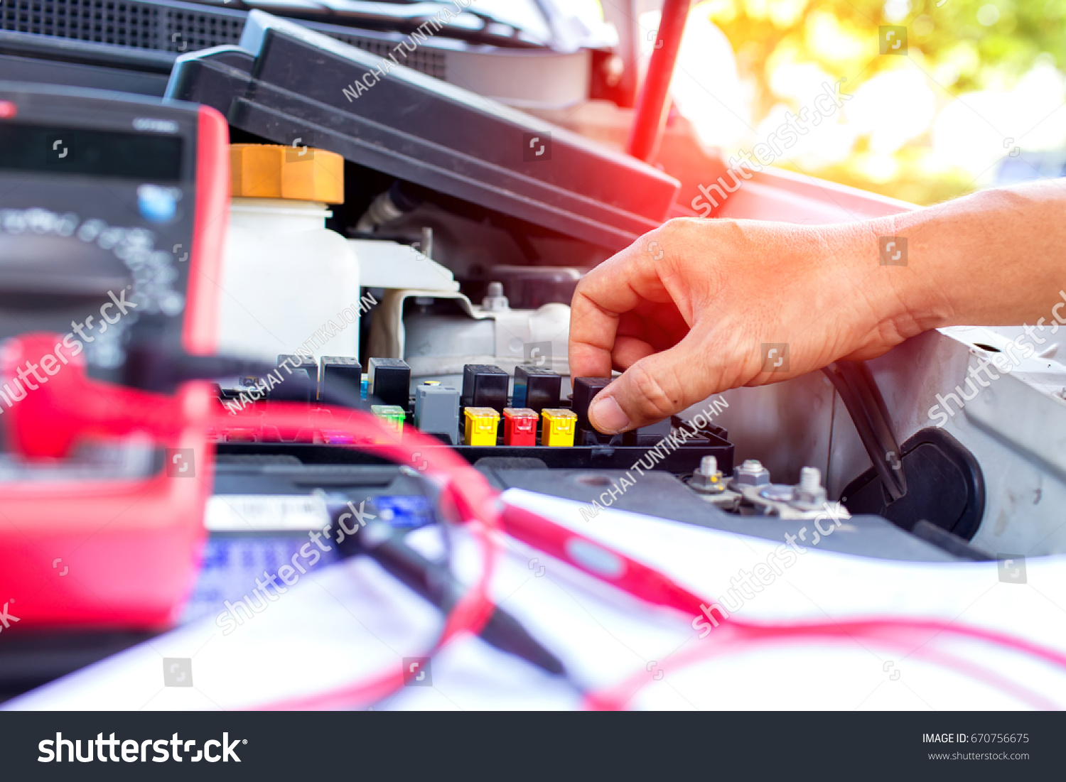 hight resolution of auto mechanic taking the hand on fuse box for check and change fuse on the