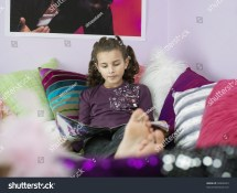 Barefoot Young Girl Reading Magazine Reclining Stock