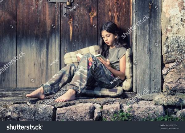 Beautiful Young Girl Enjoys Reading Book Stock