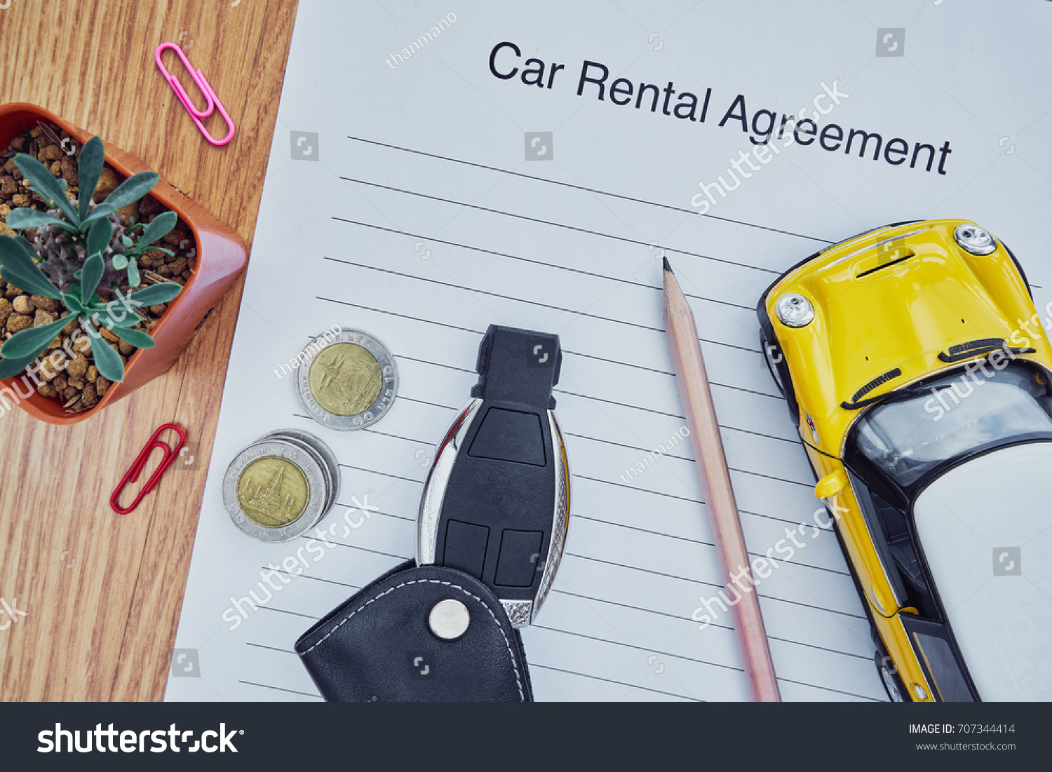 Car Rental Agreement Paper With Key, Coins And Car Model On Wooden Table