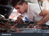 Car Repair Mechanic Fixing Auto. Man Working On Car In