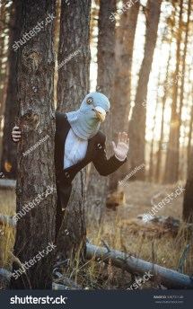 Creepy Man In Suit And Rubber Bird Mask Standing